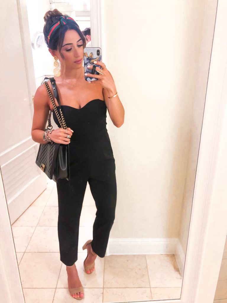 fashion blogger wearing a black strapless jumpsuit and a headband from amazon