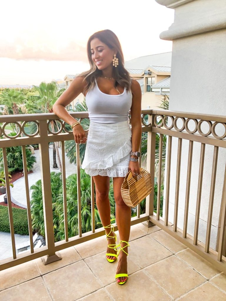 fashion blogger wearing a white eyelet ruffle mini skirt with a white tank top and neon green strappy sandals from steve madden and a bamboo bag