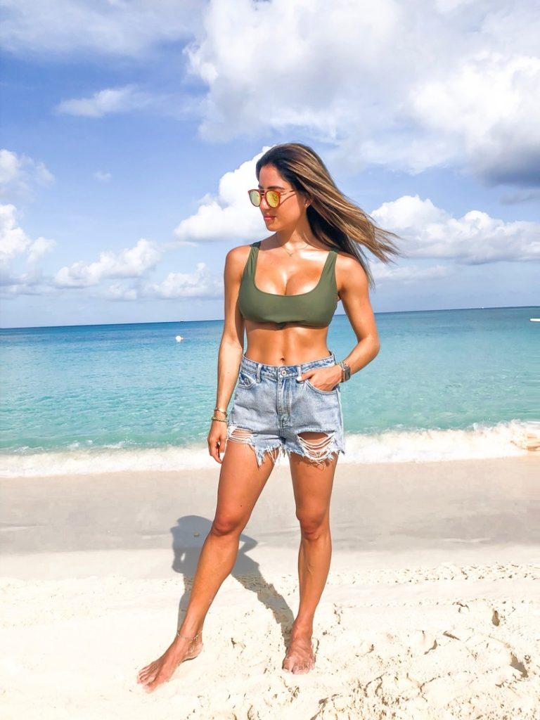 fashion blogger wearing denim cutoff shorts and an olive bikini top