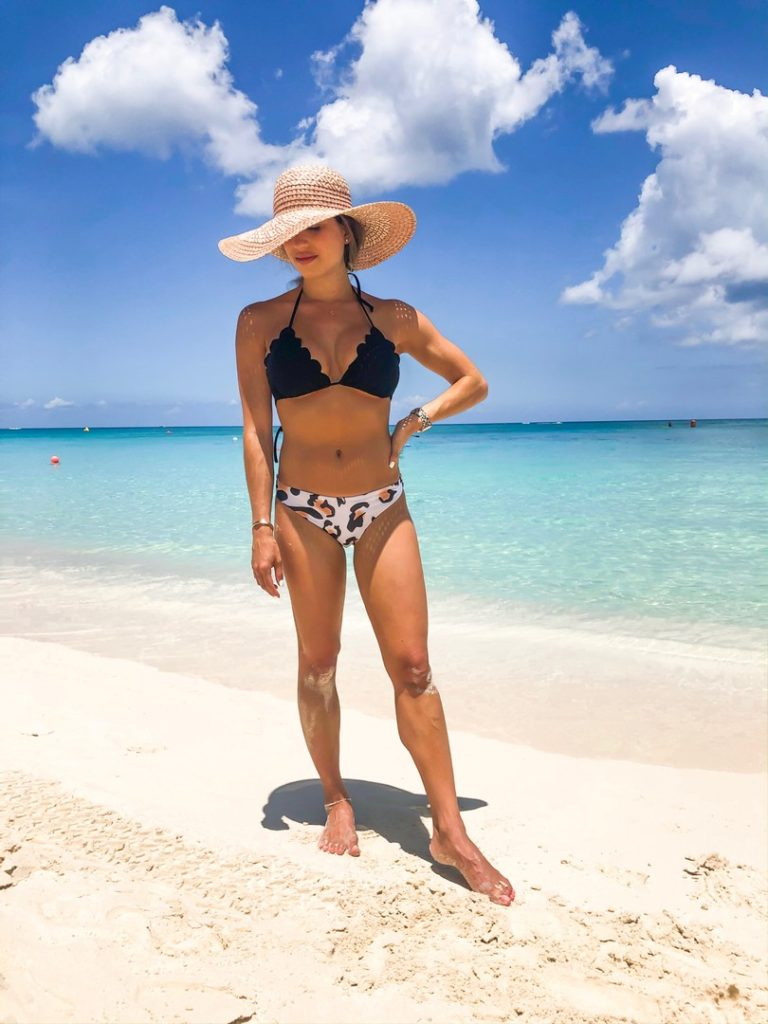 fashion blogger wearing a black scallop bikini and a leopard bikini bottom and floppy hat