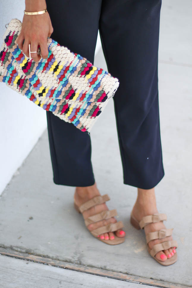 fashion blogger wearing black jumpsuit for petites with a rainbow knitted clutch from sole society, a floppy hat, and some bow neutral slide sandals | adoubledose.com