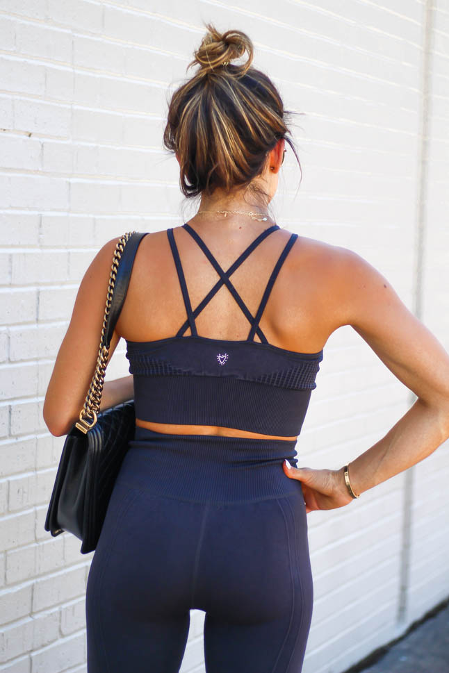 fashion and fitness blogger wearing a black strappy sports bra and laser cut leggings from betsey johnson