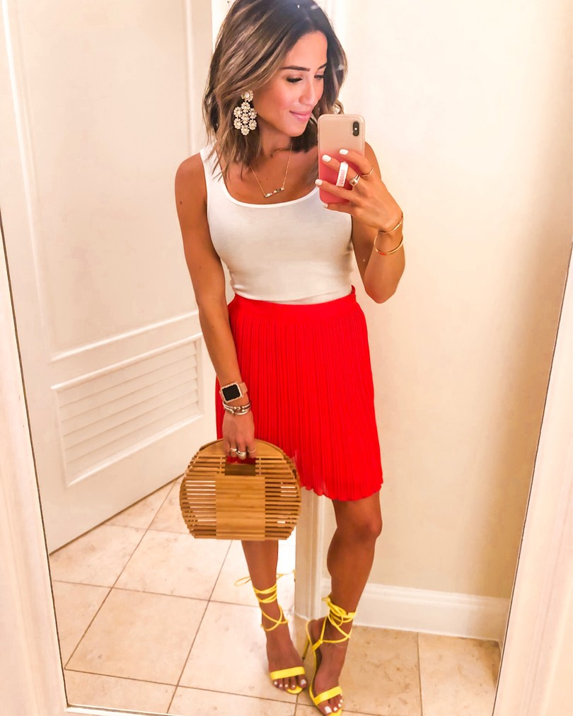 Fashion blogger wearing a red pleated skirt with a white tank and strappy neon steve madden sandals
