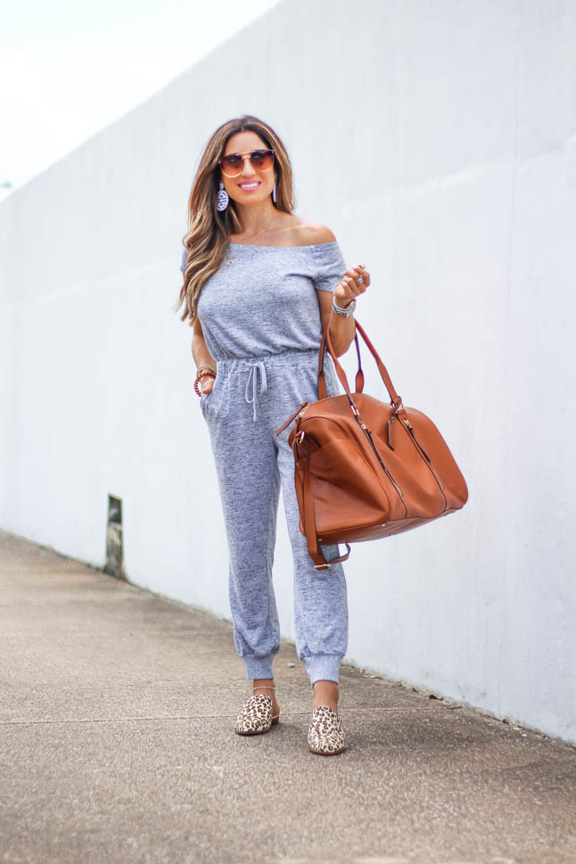 fashion blogger wearing grey jumpsuit from express with leopard printed mules from sole society and a cognac weekender travel bag with aviator sunglasses and white lisi lerch earrings