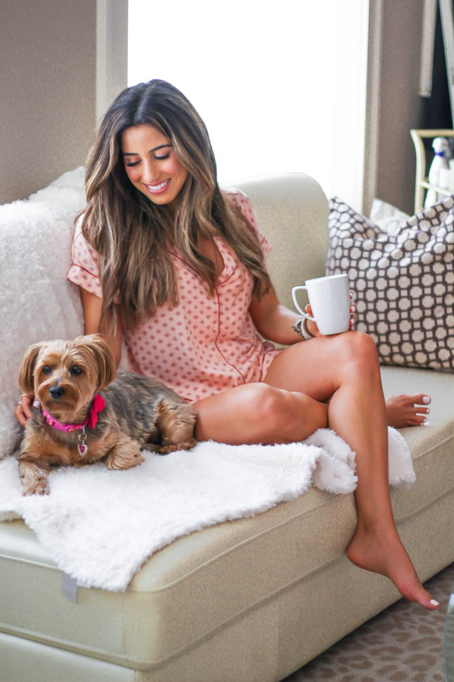 Lifestyle and fashion blogger samantha belbel of a double dose wearing pink printed short pajama set from Nordstrom with a cozy furry throw blanket barefoot dreams