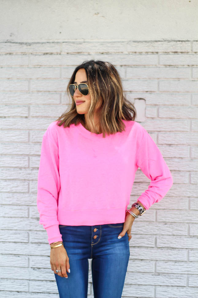 fashion and lifestyle blogger alexis belbel of adouble dose wearing a neon pink cropped sweatshirt with skinny stretchy jeans and epsadrille wedges from walmart fashion we dress america
