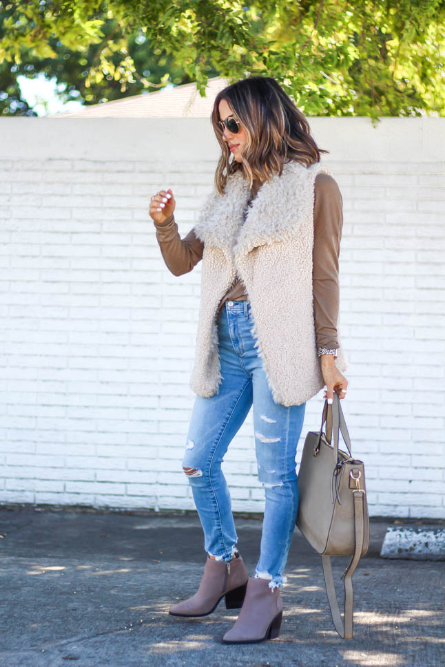 lifestyle and fashion blogger alexis belbel wearing a neutral sherpa vest from sole society with a tan long sleeve shirt and ripped jeans from abercrombie with a taupe satchel bag and pointed booties from sole society   adoubledose.com