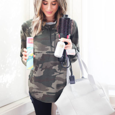 lifestyle and fashion blogger alexis belbel wearing a camo pullover and black leggings sharing her must haves for your gym bag: batiste dry shampoo, revlon hair dryer, mascara, hair ties | adoubledose.com