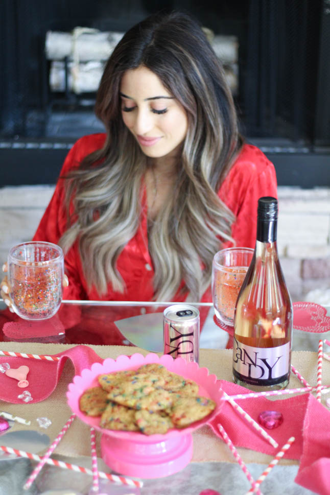 lifestyle and fashion blogger alexis and samantha belbel sharing their tips for hosting the perfect galentine's day with JaM cellars rose wine wearing red heart pajamas and festive valentines day decor| adoubledose.com