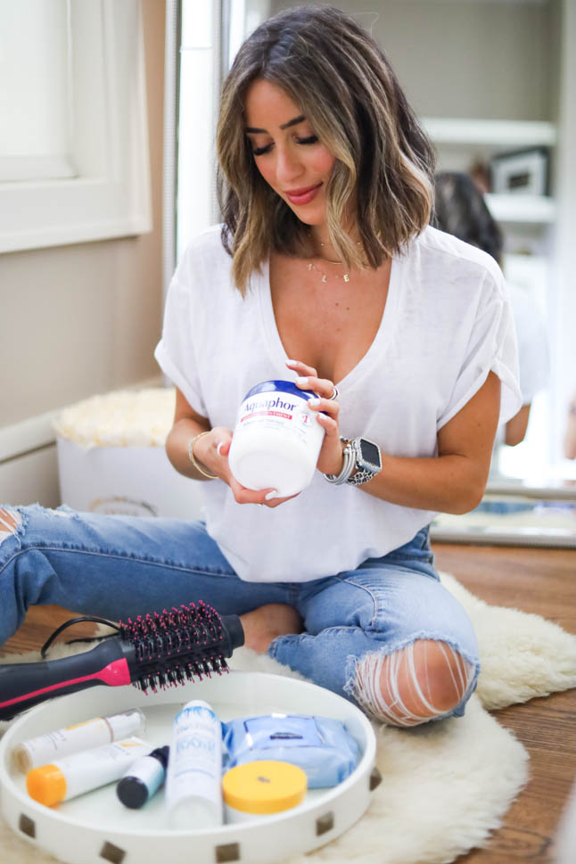 lifestyle and fashion blogger alexis belbel sharing at home beauty hacks like tricks for eyelash extensions, at home facials, self tanning, and at home manicures wearing ripped jeans and a white tee| adoubledose.com