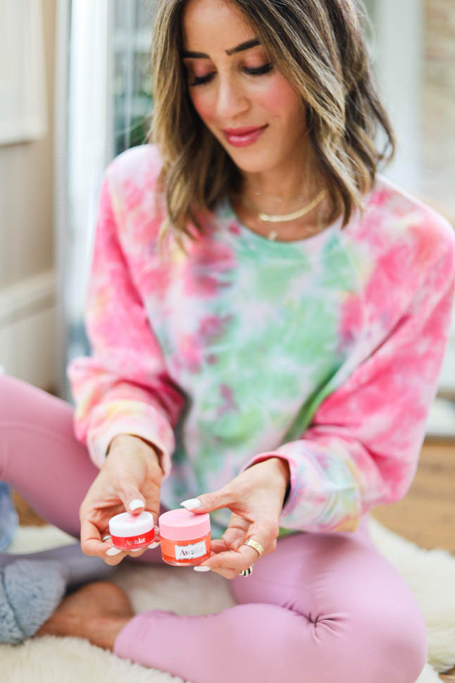 lifestyle and fashion blogger, alexis belbel wearing a tie dye sweatshirt, pink leggings, cozy slippers shares 5 Self Care Acts You Can Do During Quarantine, including awake beauty lip masks, face masks, facial exfoliators/scrubs, a back massage, and candles. | adoubledose.com